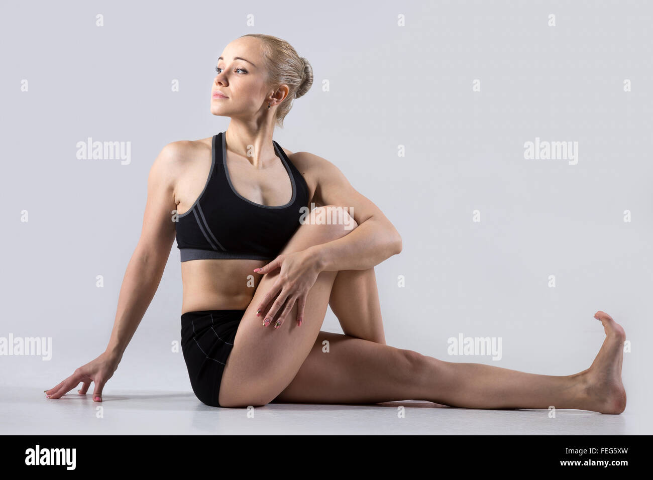Sporty beautiful young woman practicing yoga, sitting in Vakrasana, easy variation of Half lord of the fishes pose, - Stock Image
