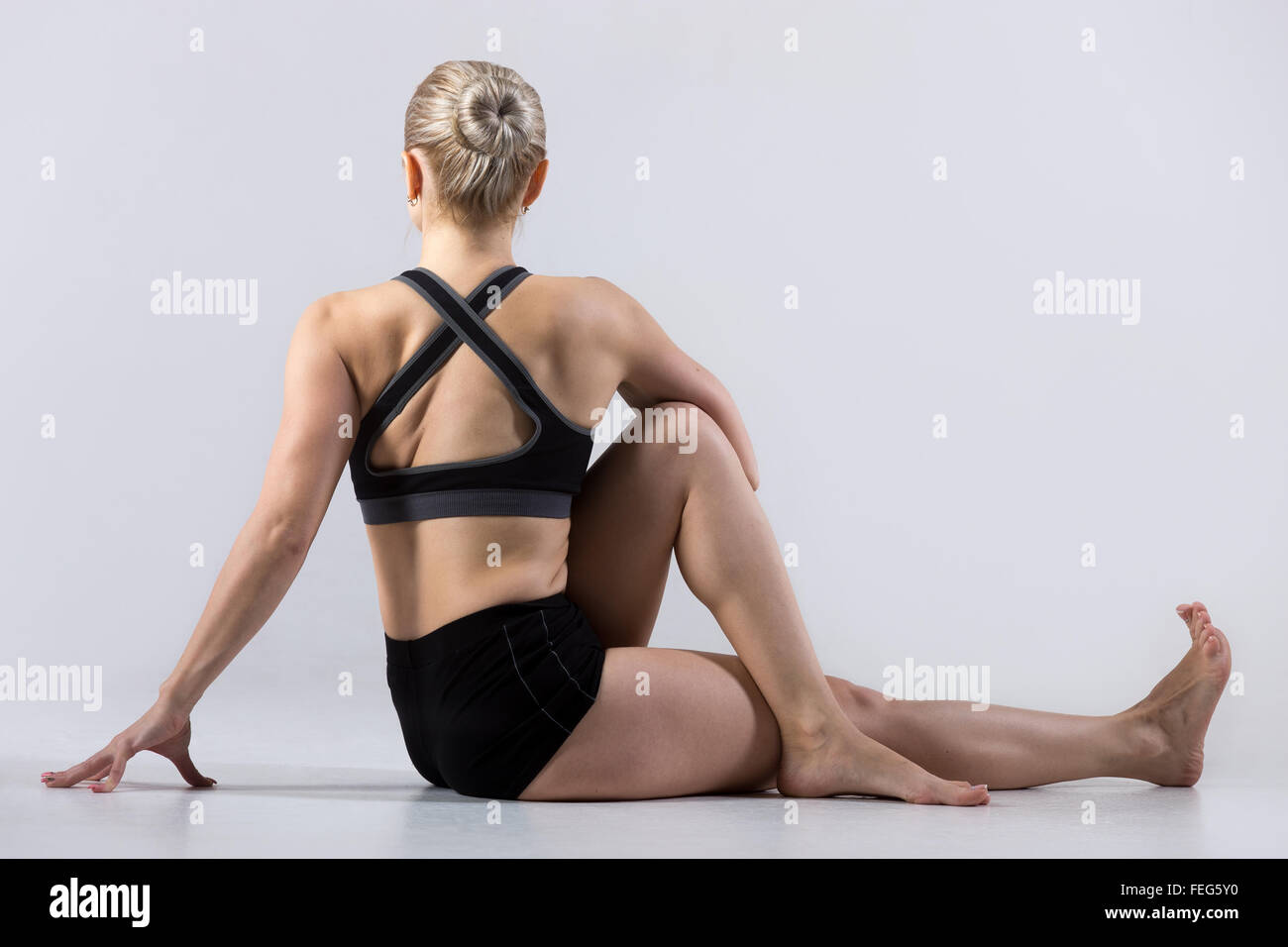 Sporty beautiful young woman practicing yoga, sitting in Vakrasana, easy variation of Half lord of the fishes pose, Stock Photo