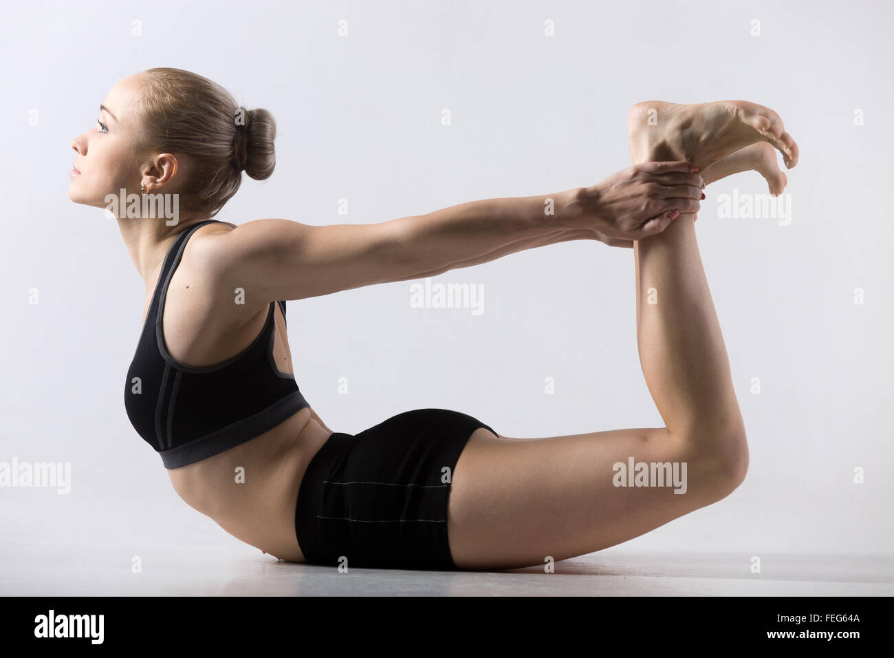 Sporty beautiful young woman practicing yoga, doing Dhanurasana, Bow Pose, working out wearing black sportswear, - Stock Image