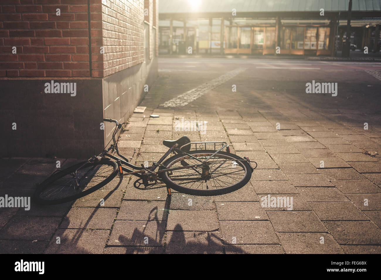 Old bicycle left and forgotten on city street pavement - Stock Image