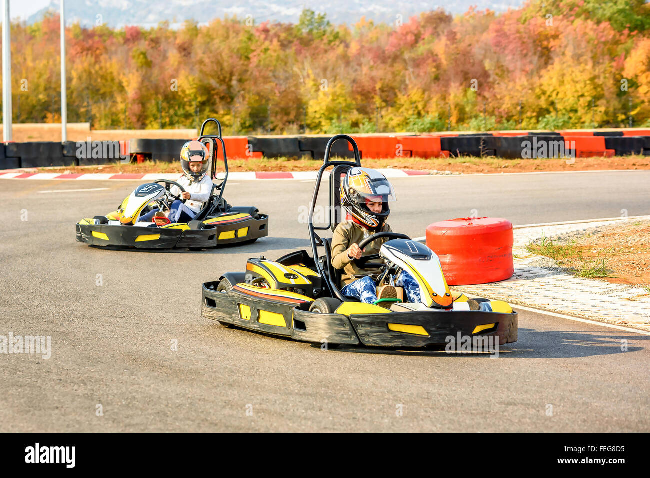 Little girls are driving Go- Kart car in a playground racing track Stock Photo