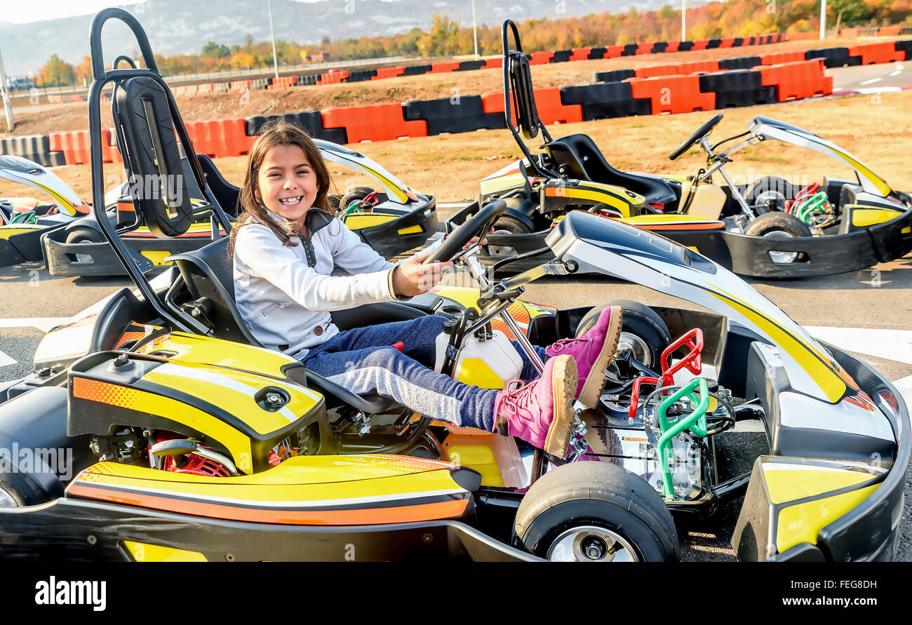 Little girl is driving Go- Kart car in a playground racing track Stock Photo