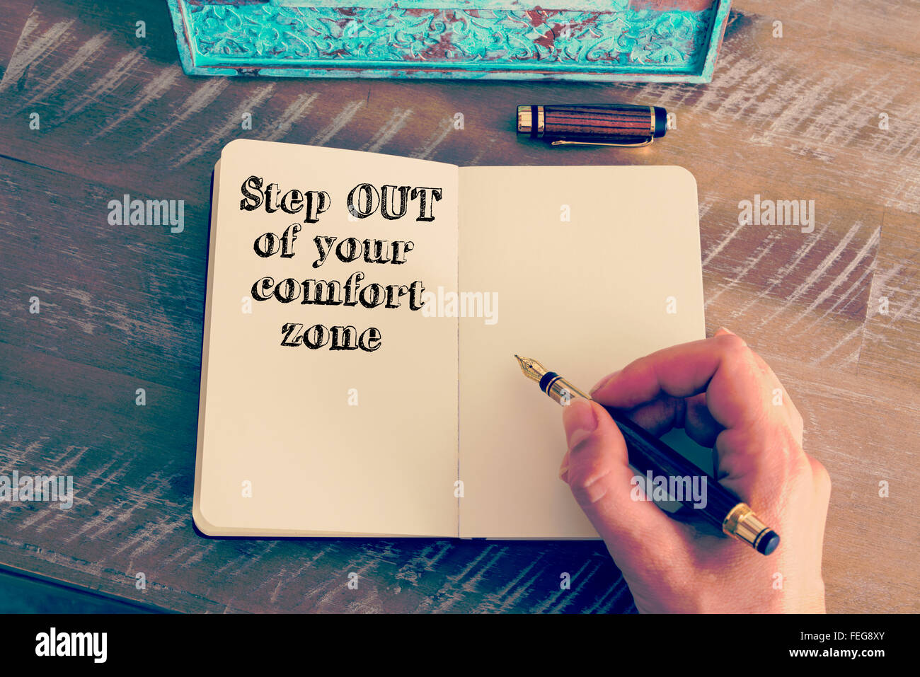 Retro effect and toned image of a woman hand writing a note with a fountain pen on a notebook. Stock Photo