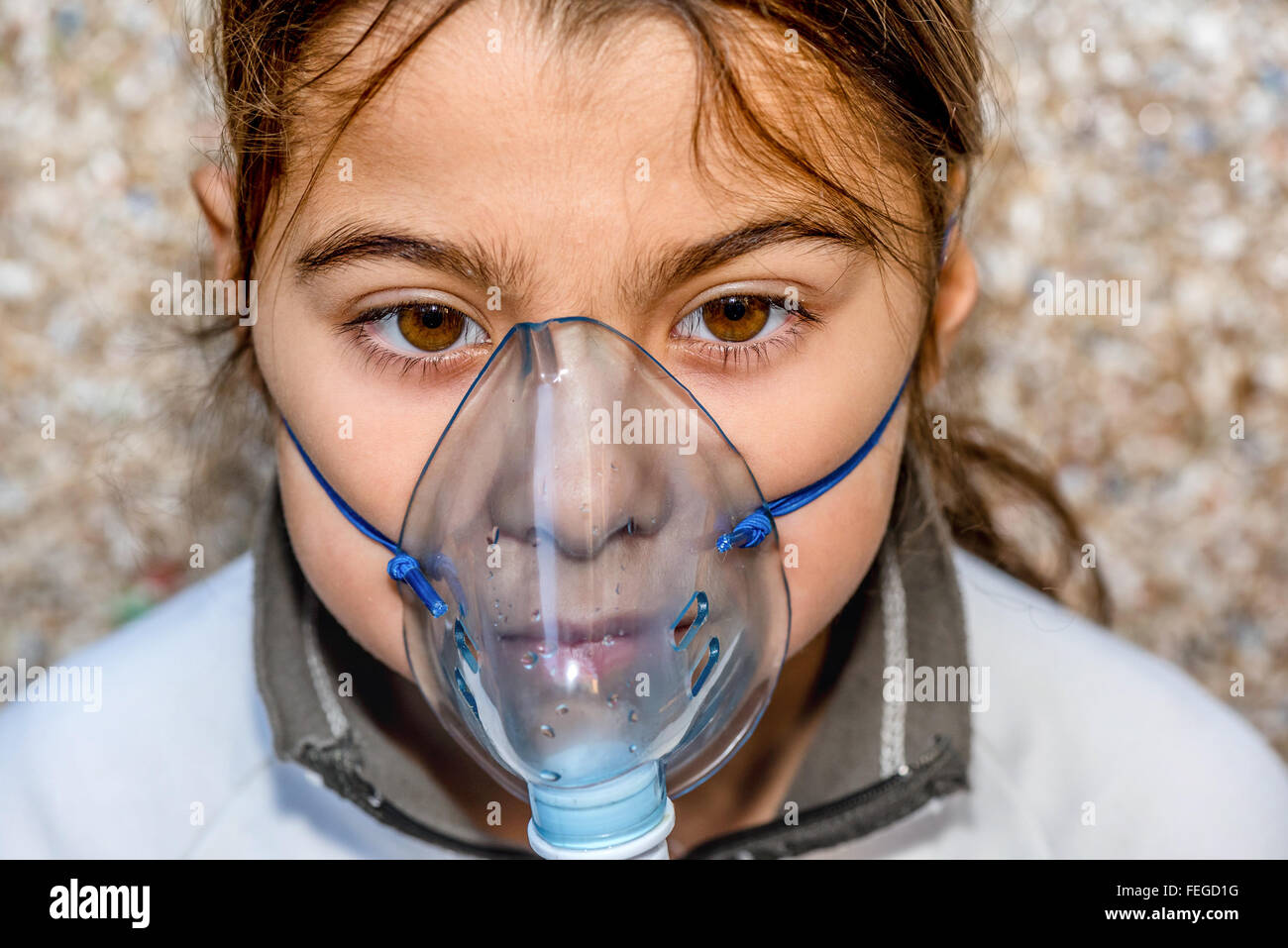 Eight years old kid with bronchitis inhaling medication - Stock Image