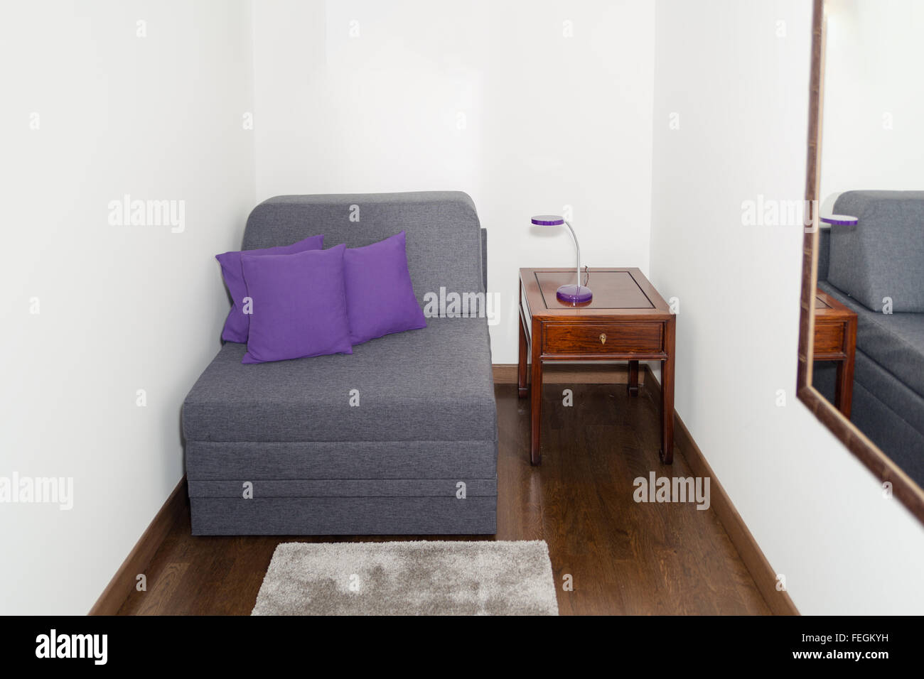 Comfy Gray Armchair with Purple Pillow near a Small Table with Modern Night Lamp. Armchair in a Small Room for Guests - Stock Image