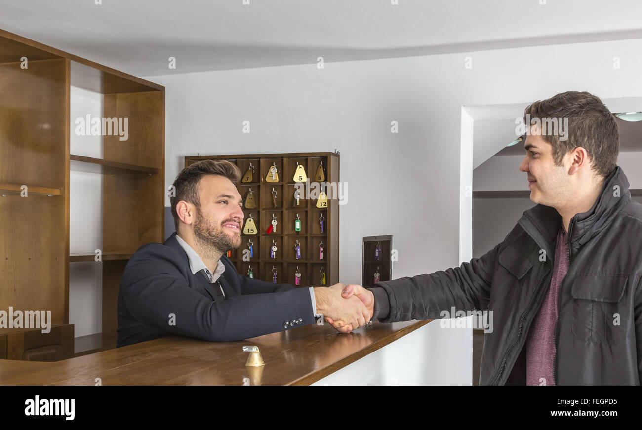 The receptionist and a client shaking hands at the hostel reception desk. - Stock Image