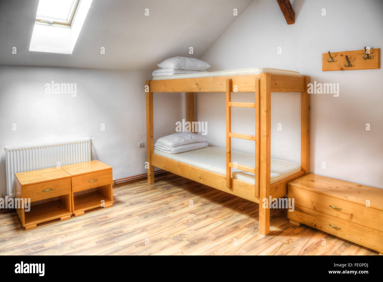 Clean hostel room with wooden bunk beds. - Stock Image