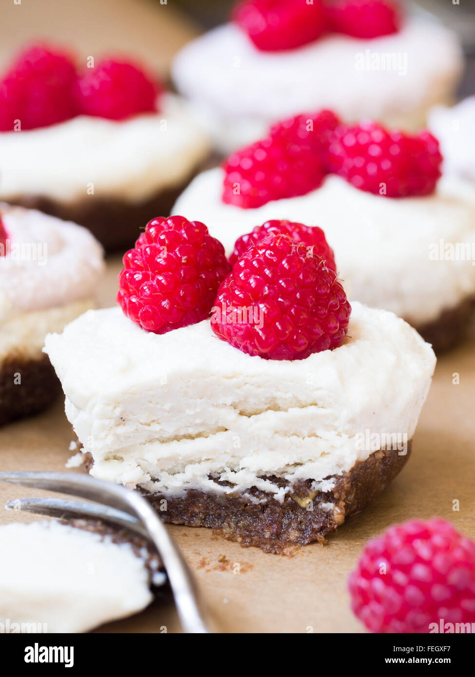 Raw vegan mini 'cheesecakes' made of cashew nuts, coconut cream and dates, served with raspberries. Close - Stock Image
