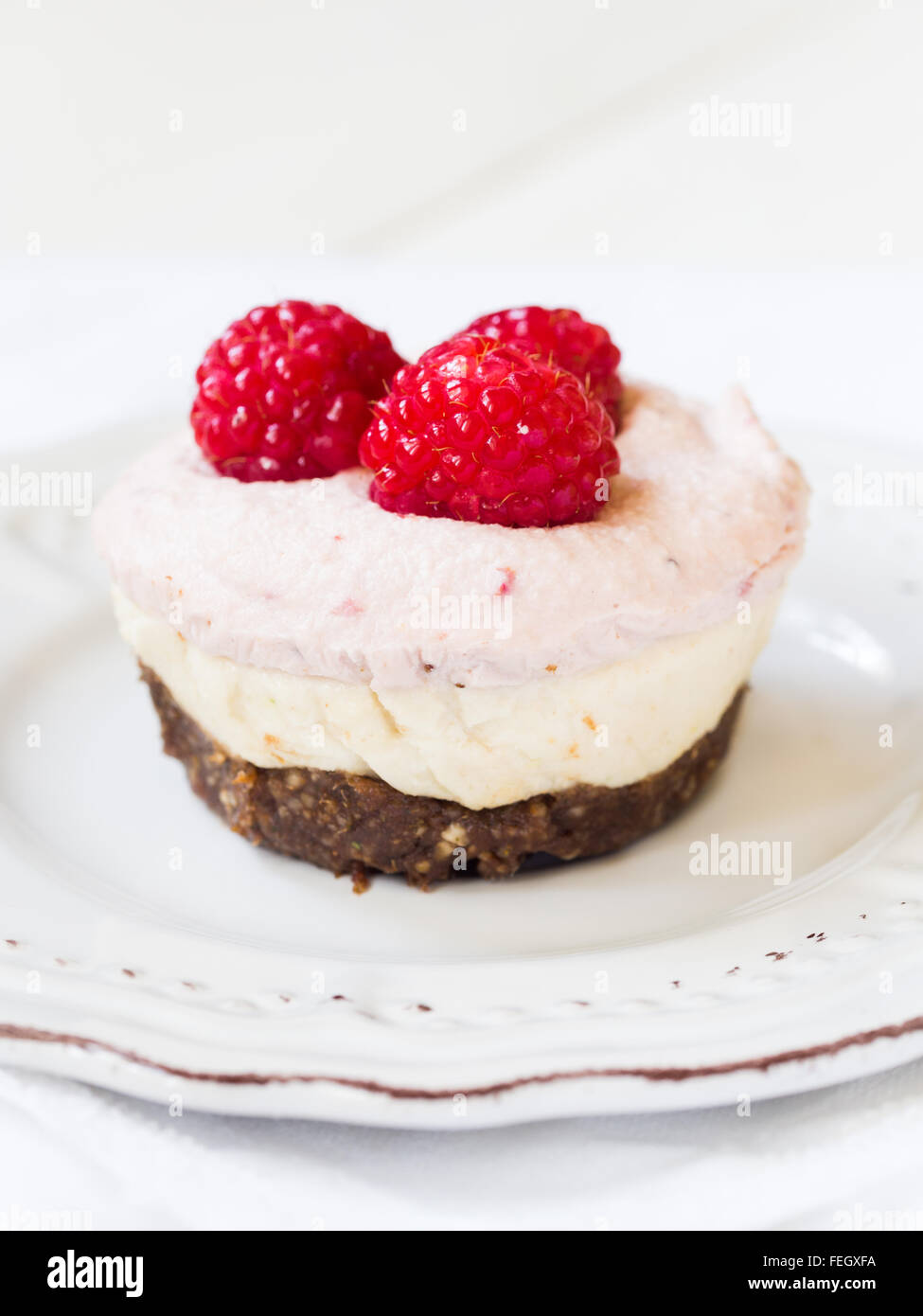 Vegan mini three colors 'cheesecake' made of cashew nuts, coconut cream and dates, served with raspberries. - Stock Image