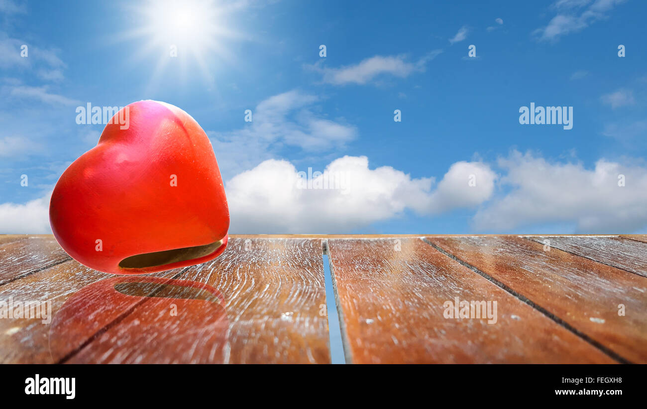 Heart on wooden table texture and beautiful sky background. - Stock Image