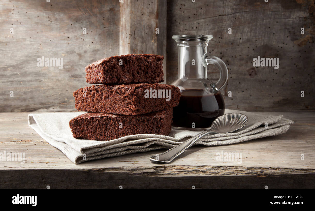 brownies and chocolate sauce with a spoon on a napkin Stock Photo