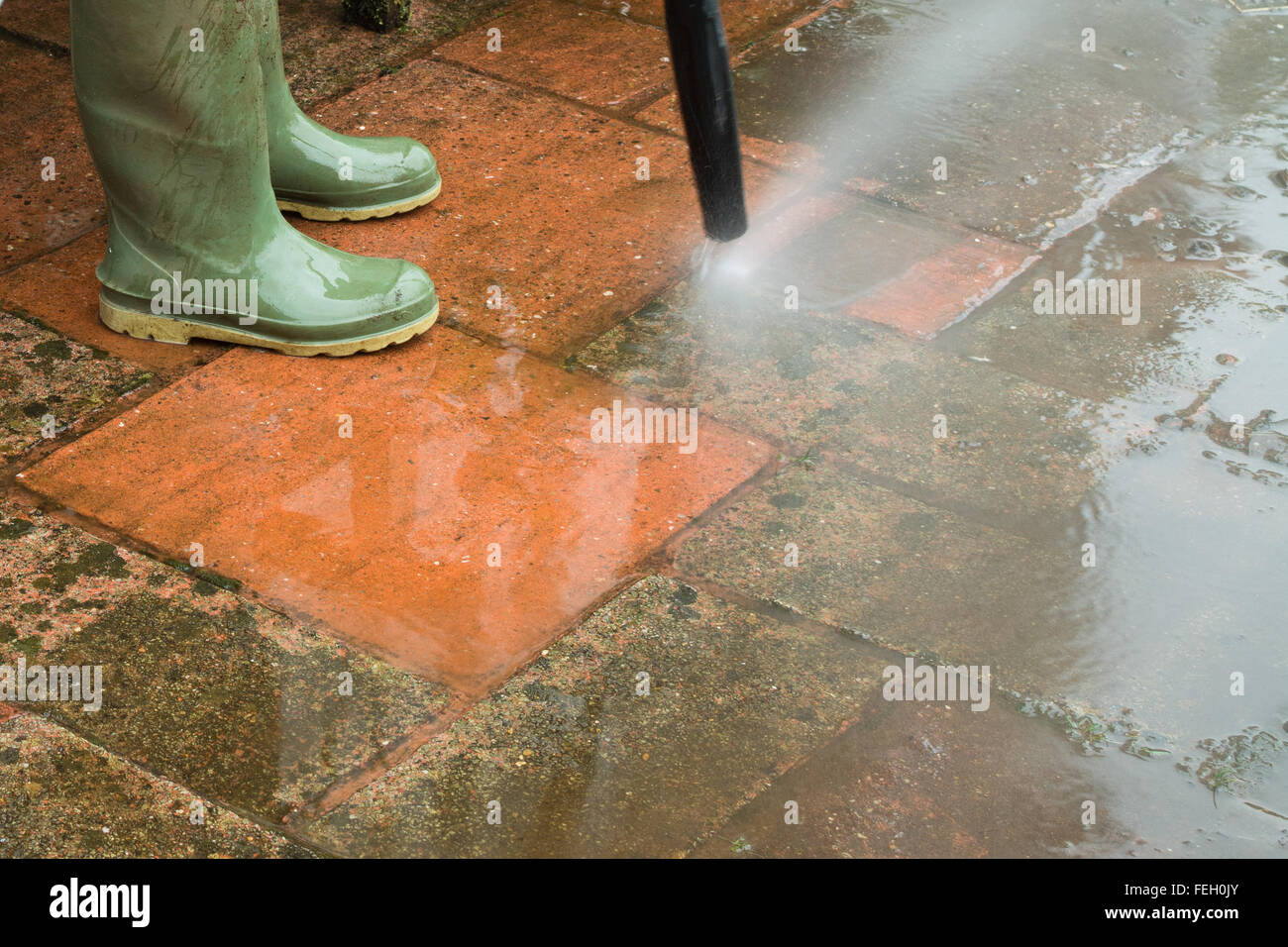 Power washing dirty patio - Stock Image