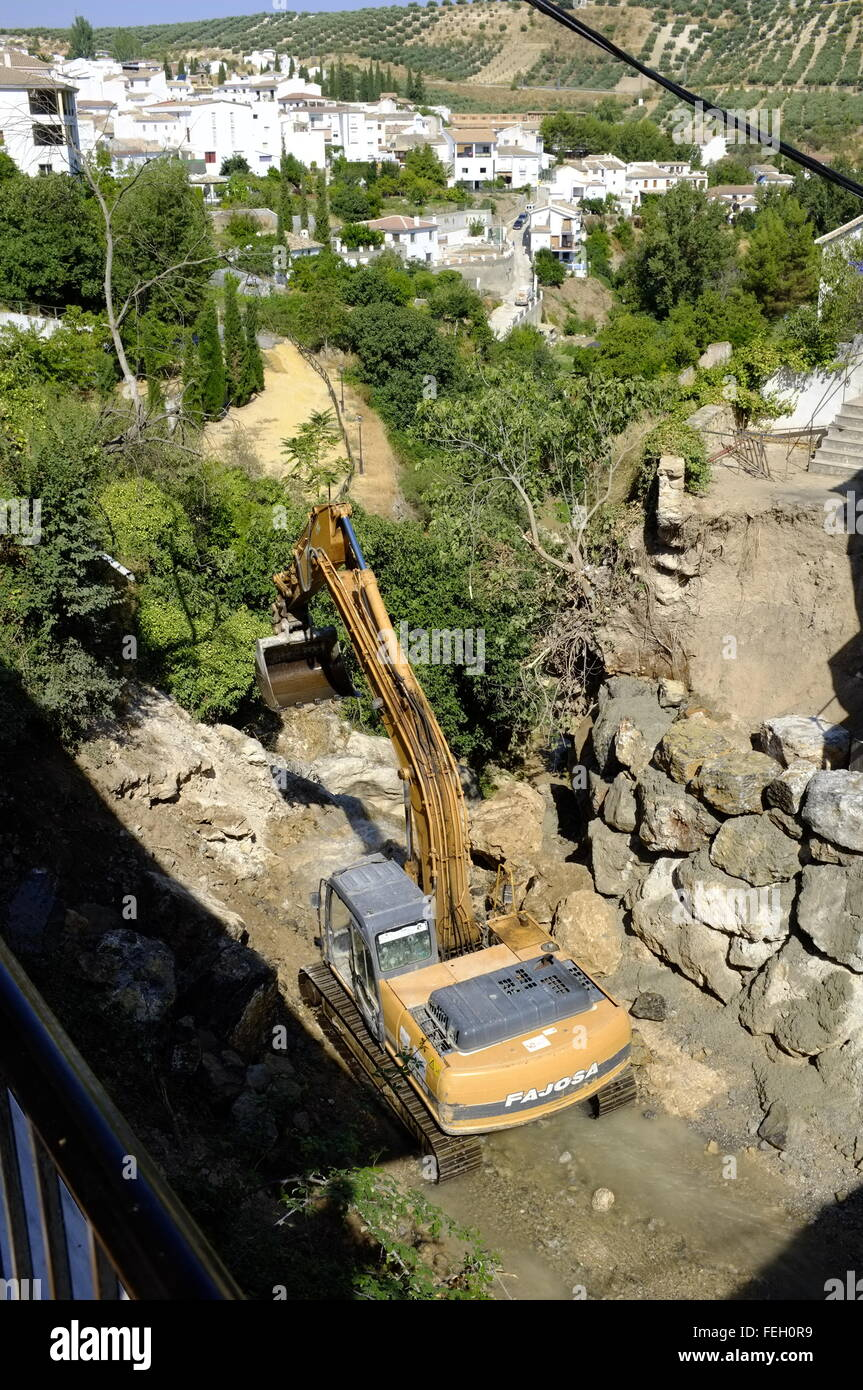Digger lowered into a river canyon to remove or re-site rocks washed down by flood. Almedinilla, Cordoba. Spain - Stock Image