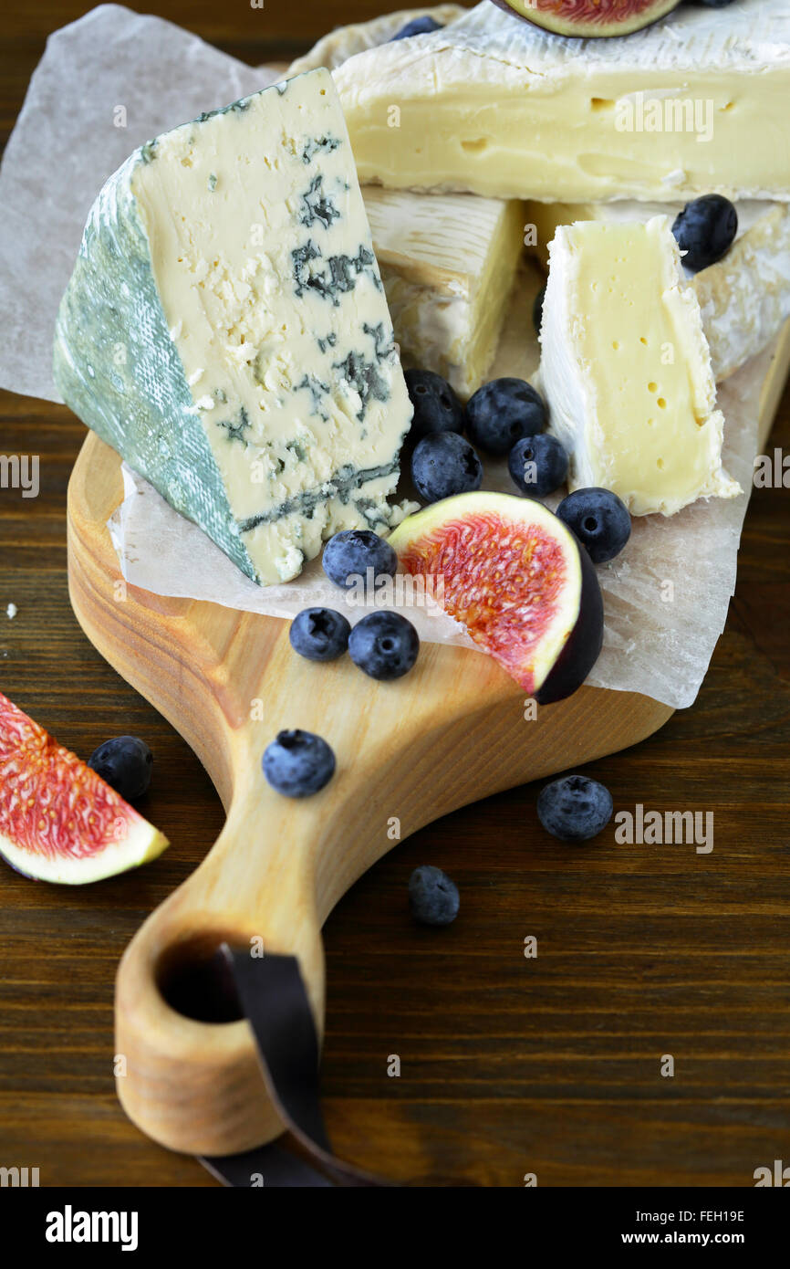 blue cheese and brie with fruits, food closeup - Stock Image