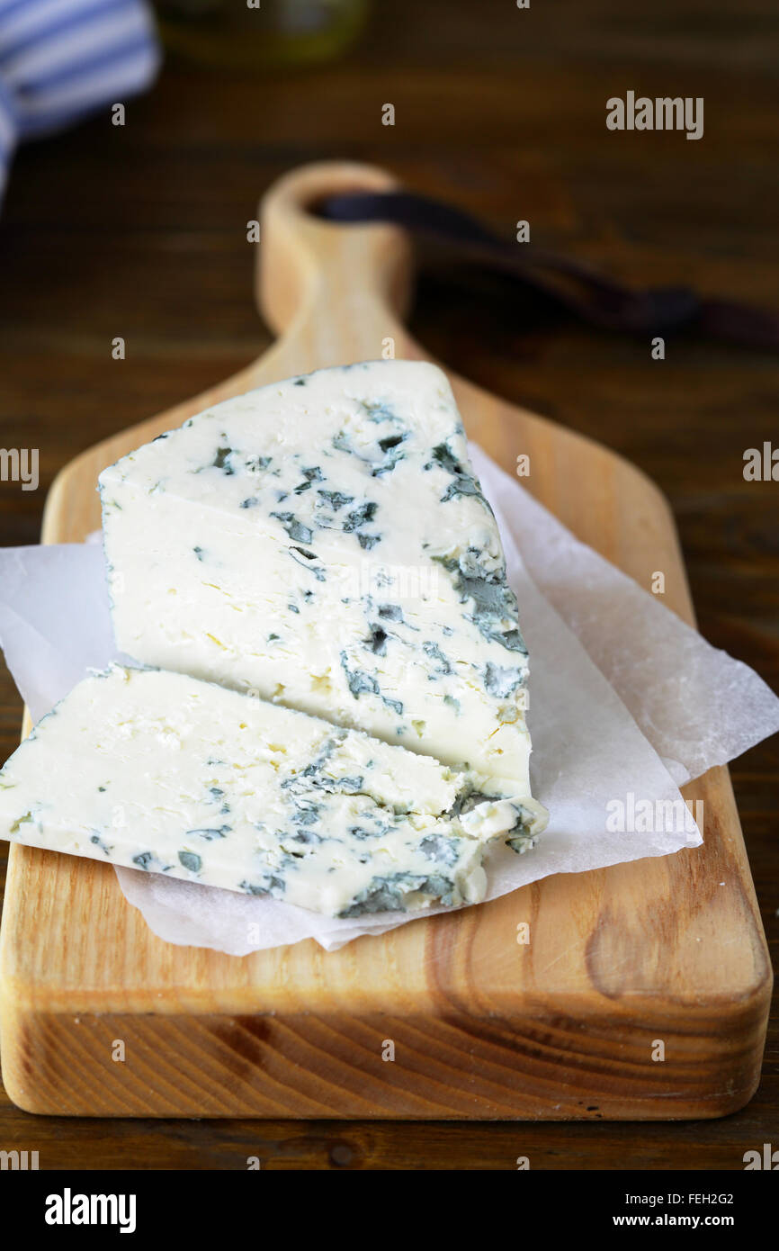 Roquefort cheese on chopping board, food closeup - Stock Image