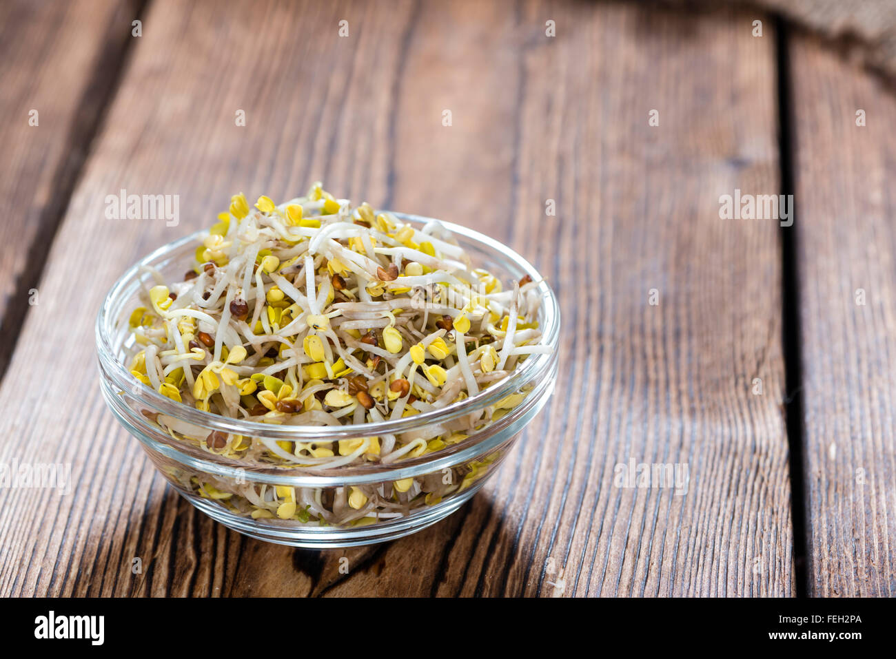 Some fresh Radish Sprouts on rustic wooden background - Stock Image