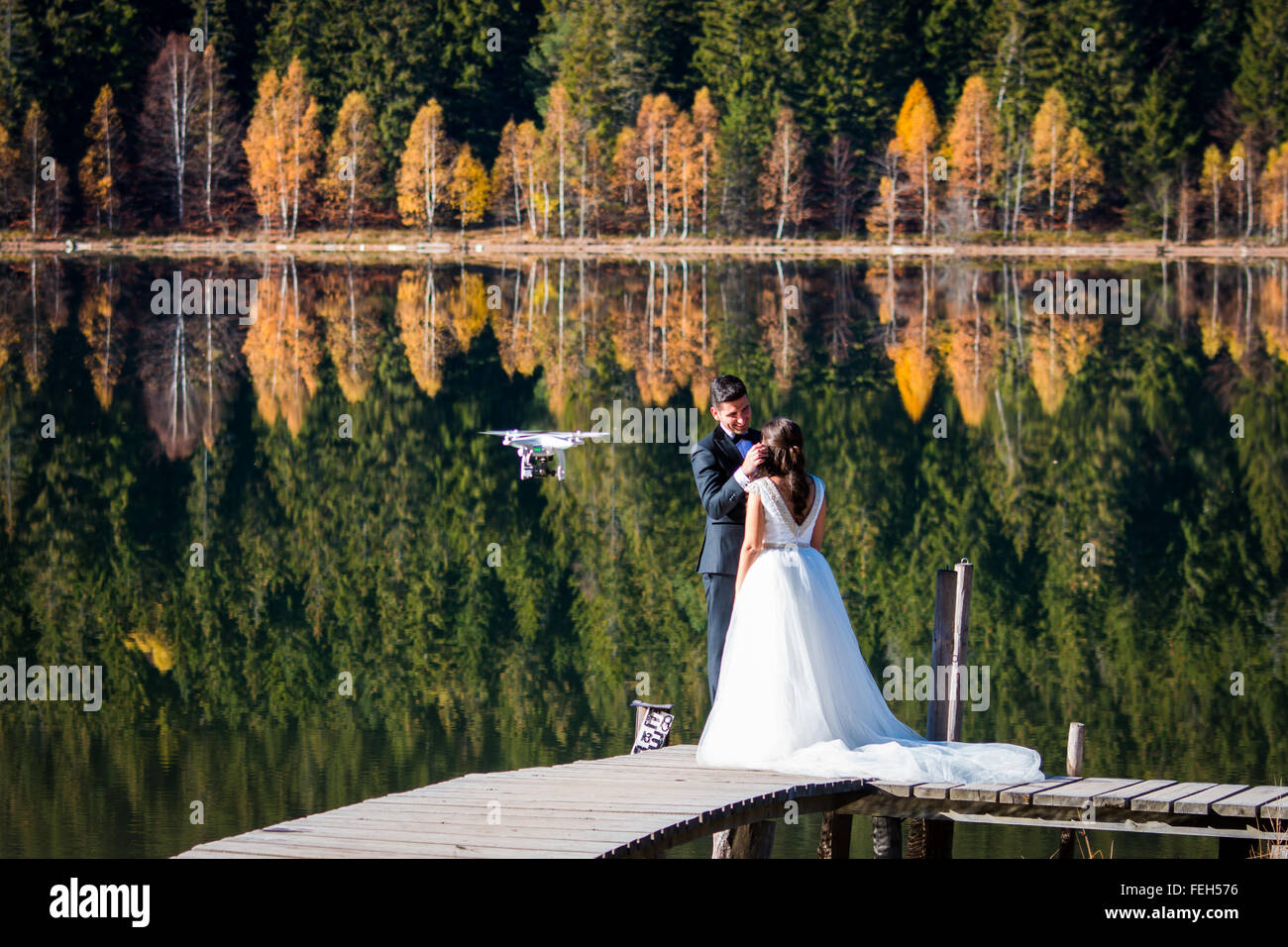 Groom and bride being filmed by a drone on the shore of a lake in an autumn setting - Stock Image