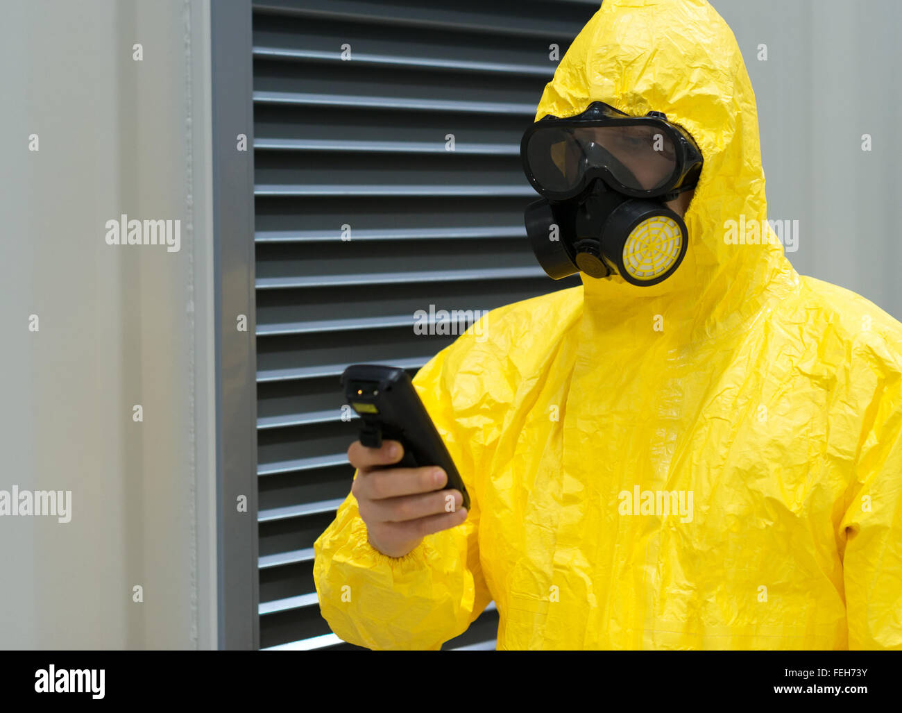 Worker in protective chemical suit checking radiation with geiger counter. - Stock Image