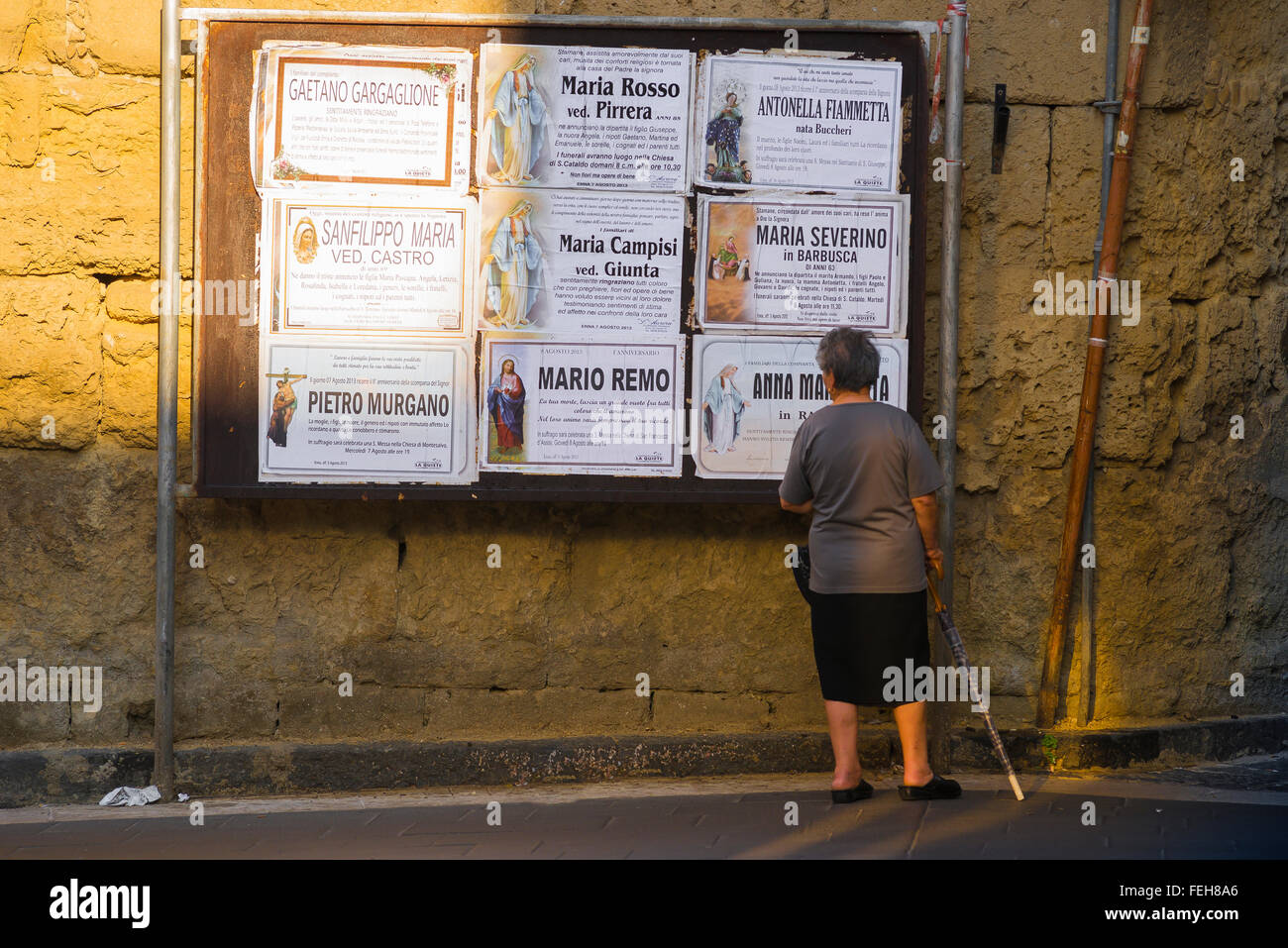 A senior local woman in Enna, Sicily, pauses to read the latest public notifications of funerals in the community. - Stock Image