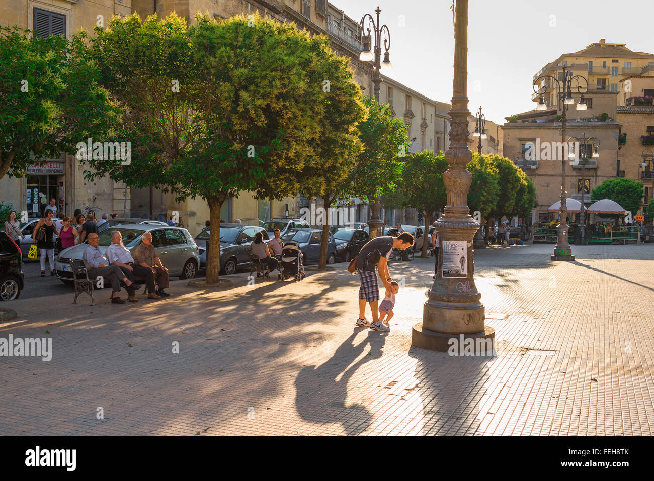 Father child Italy, at the end of a summer day in the Piazza Vittorio Emanuele in Enna, Sicily, a young father helps - Stock Image