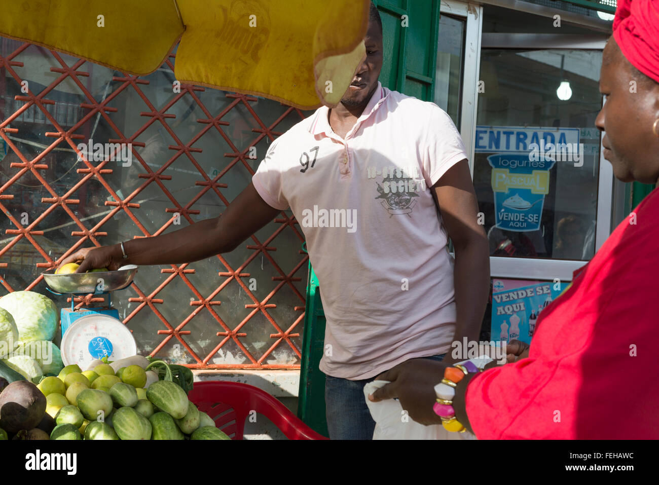 A market trader weighing lemons for a woman in the Guinea Bissau captial city of Bissau - Stock Image