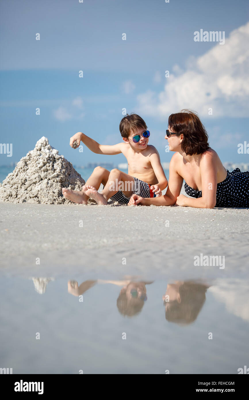 Young mother and her little son building sand castle at beach in Florida Stock Photo