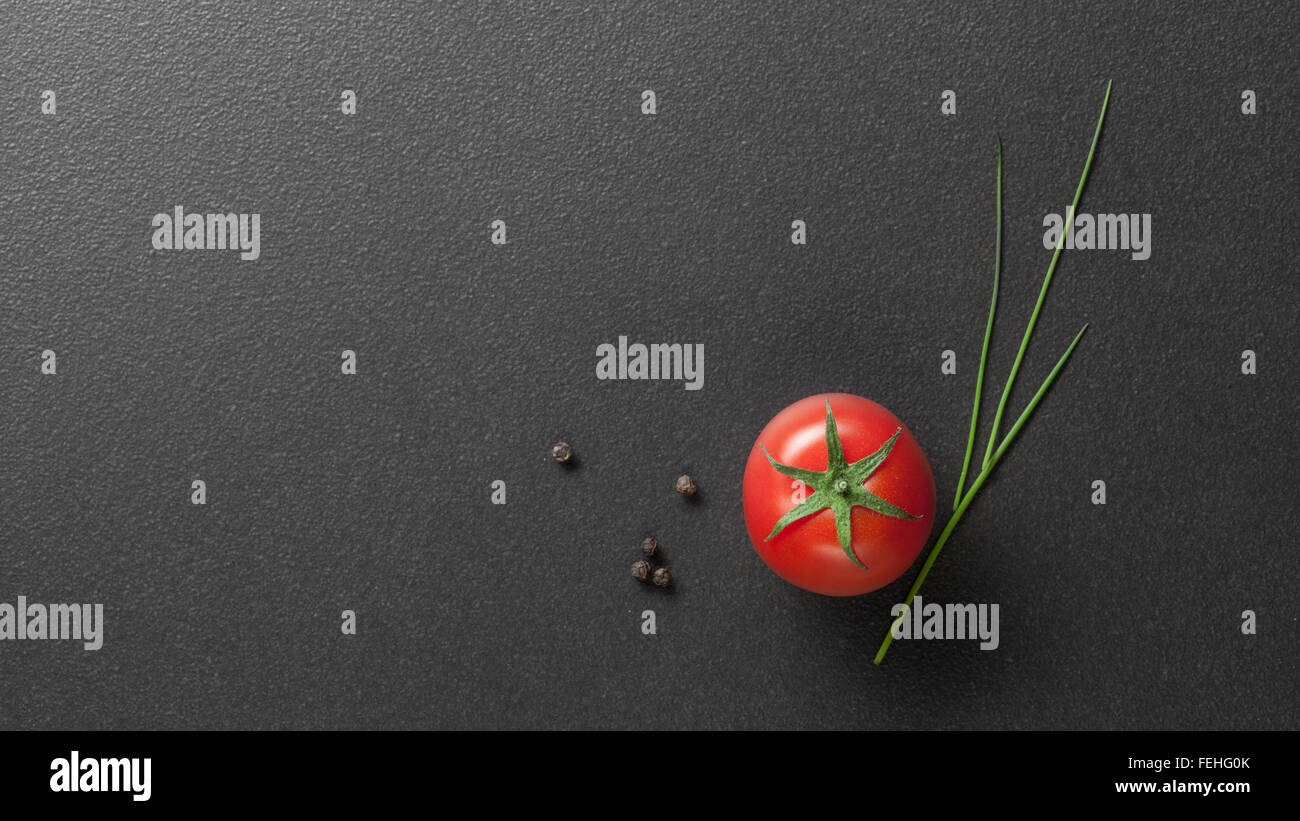 red tomato with green onion on black - Stock Image