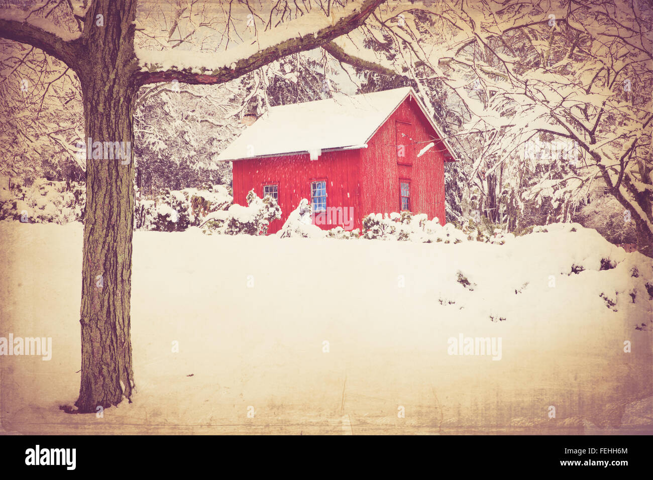 Retro style image of red barn in winter with snow and trees. this image has a vintage texture effect. Stock Photo
