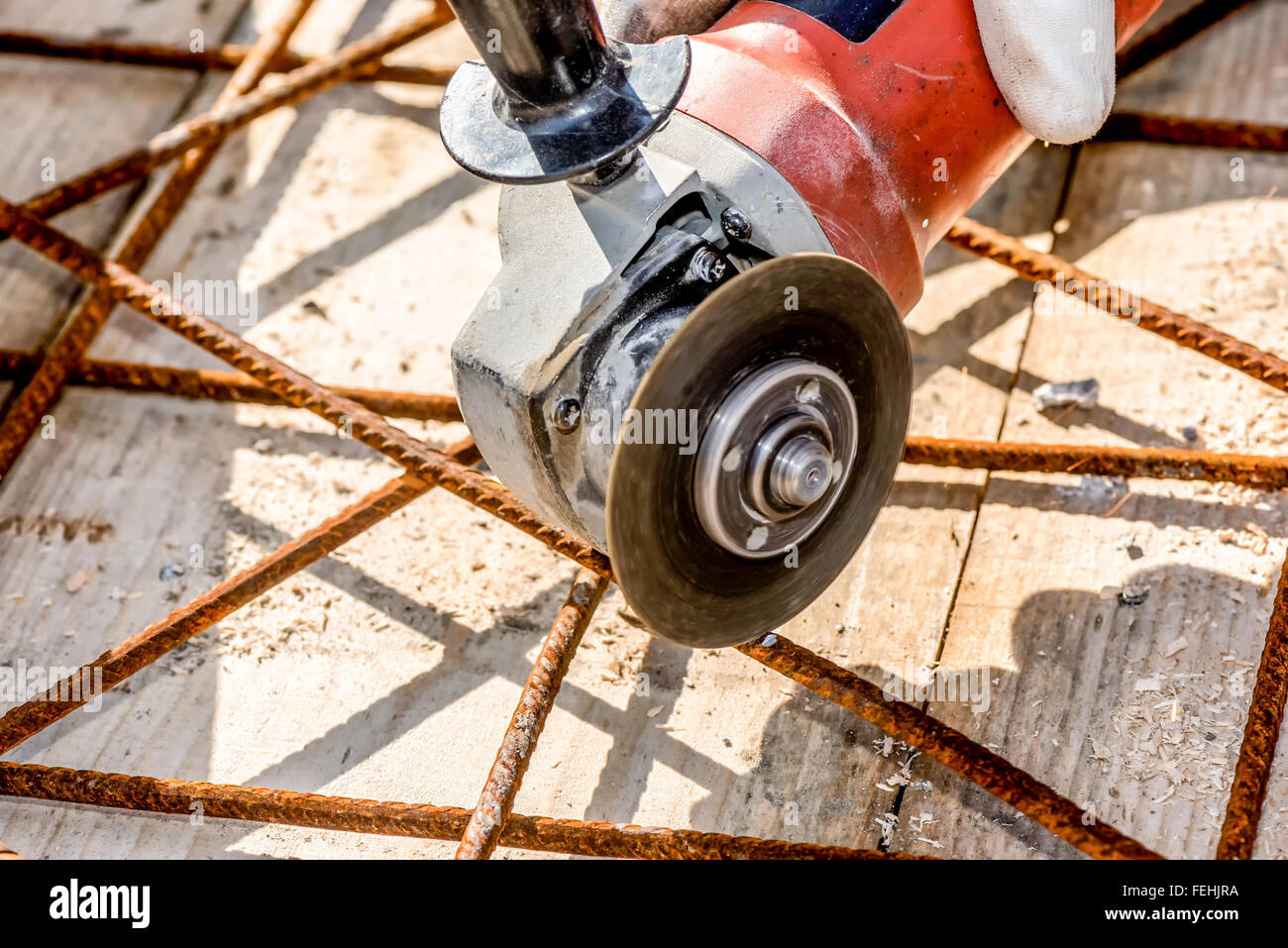 Worker cutting construction  steel net with Angle Grinder Machine closeup - Stock Image
