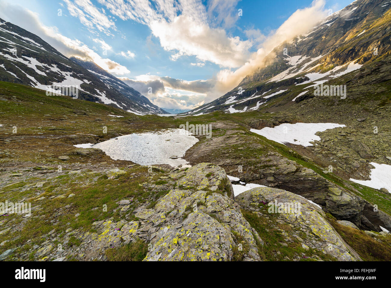 Flowing waters from melting snow feeding high altitude alpine lake in idyllic uncontaminated environment once covered - Stock Image