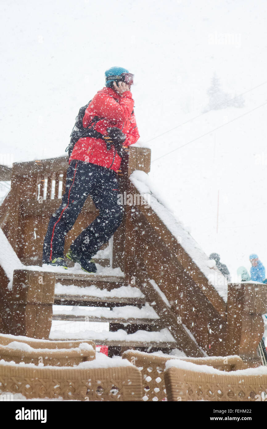 Man on his mobile phone in falling snow on ski holiday in ski resort of Courchevel, France, Europe - Stock Image