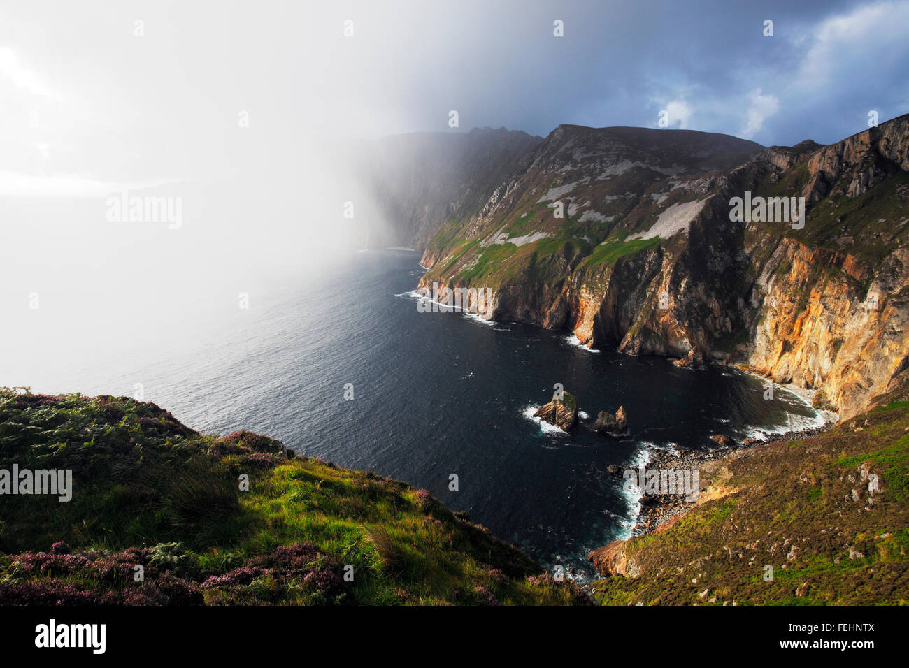 heavy rain shower in front of the sunset at Slieve League (Irish: Sliabh Liag)  601 metres (1,972 ft) high sea cliffs - Stock Image