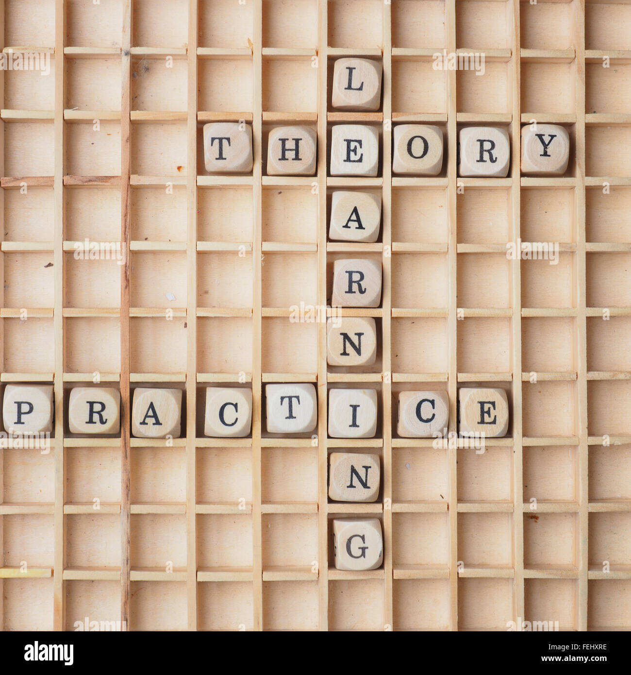 Learning concept with wooden dices and the words theory and practice - Stock Image