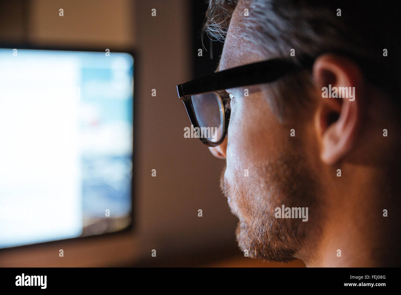 Serious stubbled young man in glasses using computer and looking at screen - Stock Image