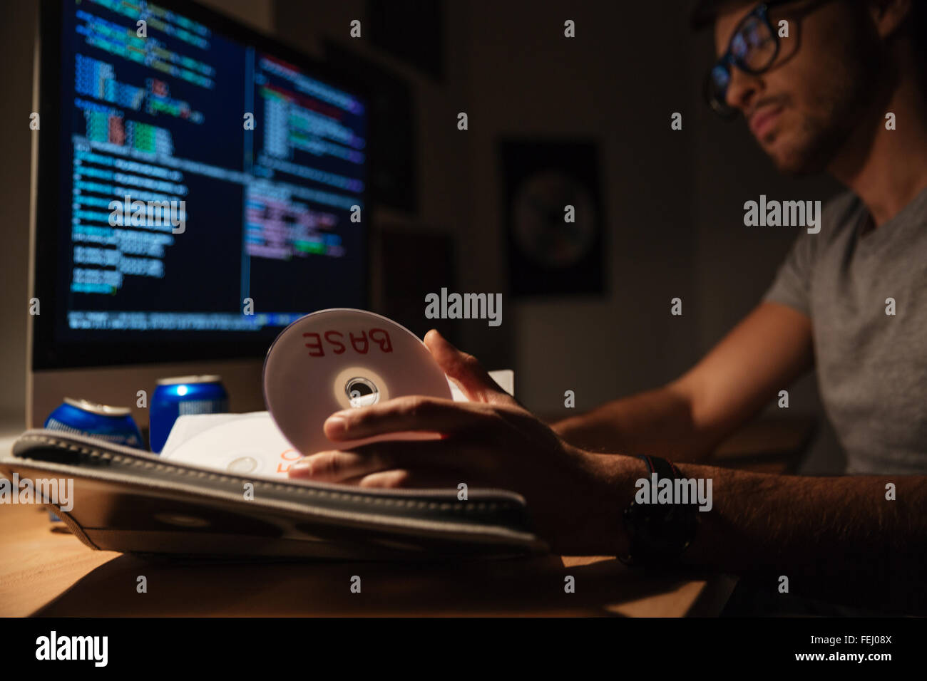 Confident young programmer taking cd with base and coding on computer in dark room - Stock Image