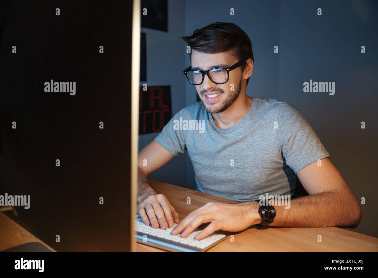 Happy attractive young man in glasses sitting and typing on computer at home - Stock Image
