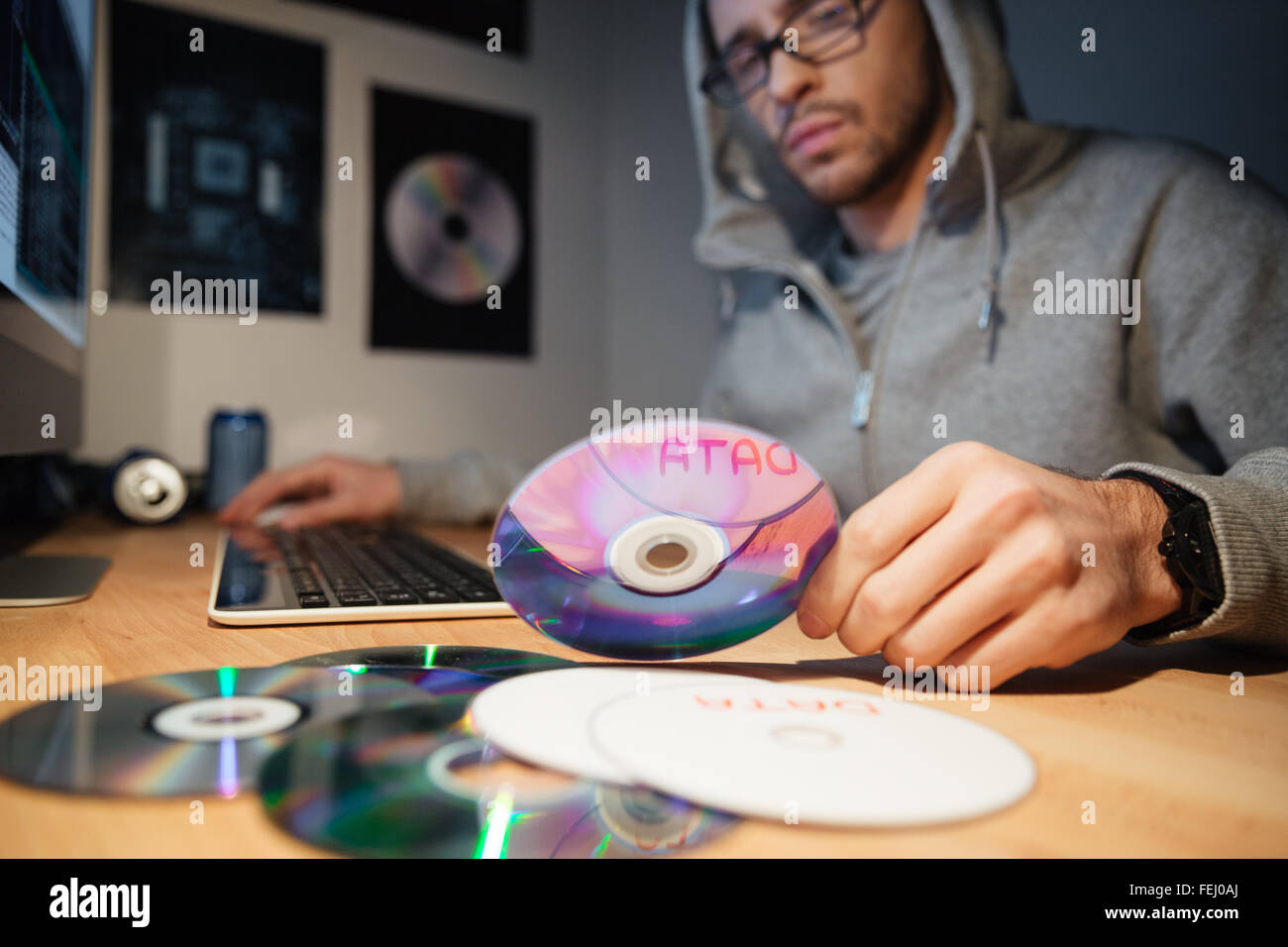 Confused thoughtful young software developer in hoodie and glasses working at home and choosing CD with database - Stock Image