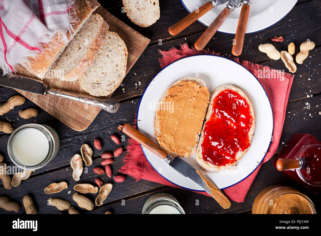 Peanut butter and jelly sandwich on a rustic table. Photographed from directly above. - Stock Image