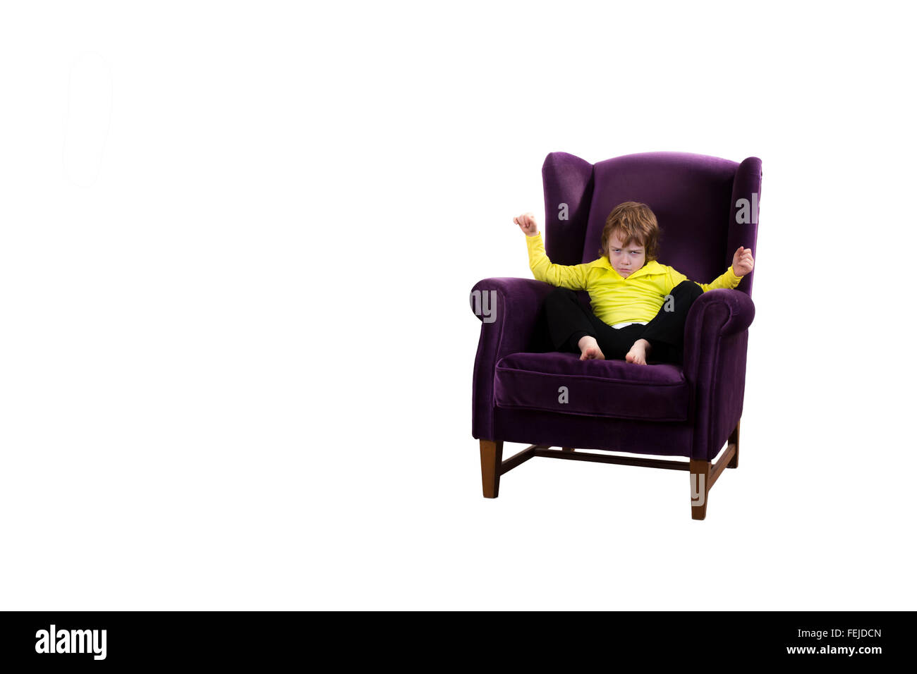 angry red hair child sitting on the purple couch - Stock Image