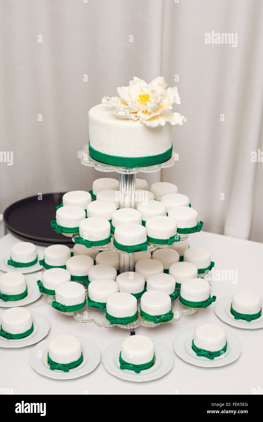 white wedding cake with green details and cupcakes Stock Photo ...