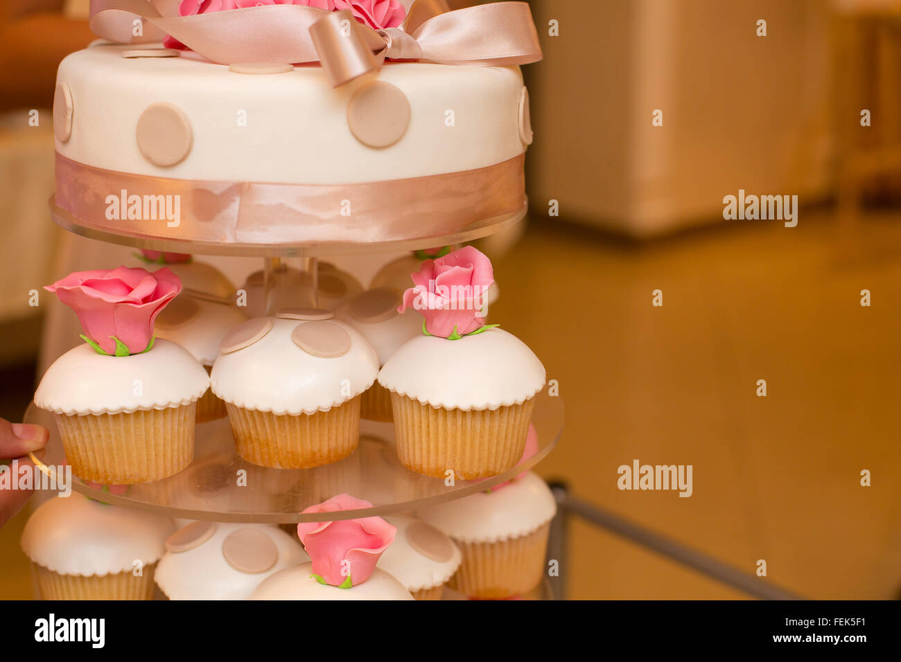 White wedding cake and pink flowers and cupcakes stock photo white wedding cake and pink flowers and cupcakes mightylinksfo Image collections