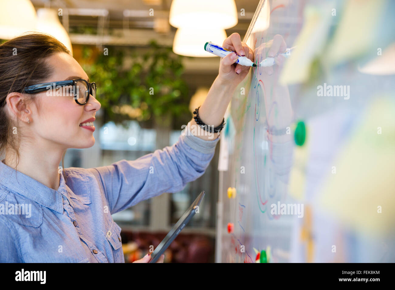 Smiling businesswoman writing something on whiteboard in office - Stock Image