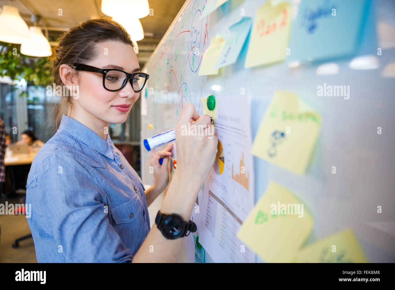 Young woman writing business plan on whiteboard in office - Stock Image
