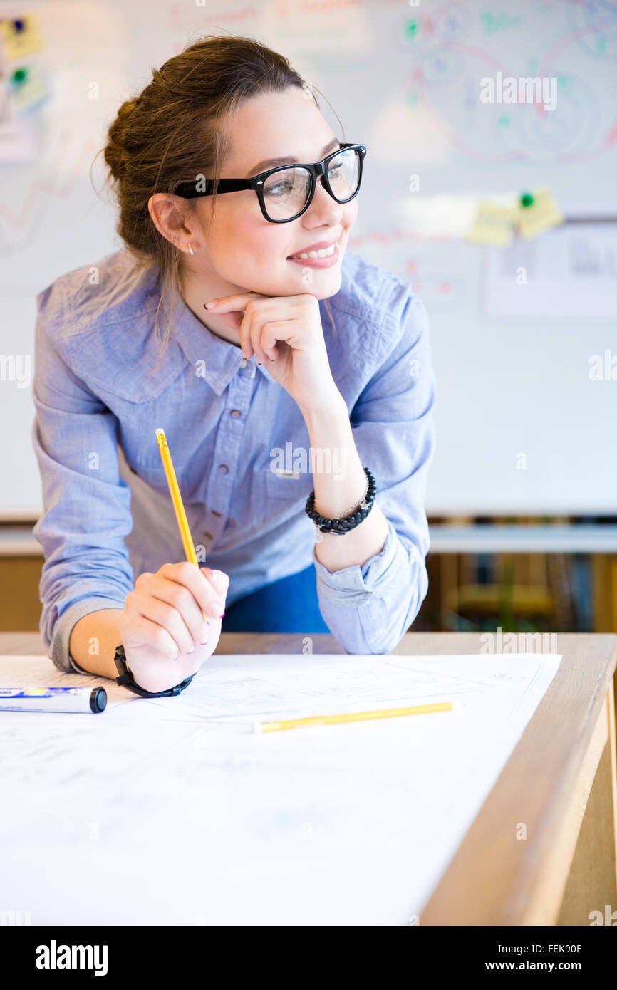 Inspired beautiful young business woman in glasses working in office - Stock Image