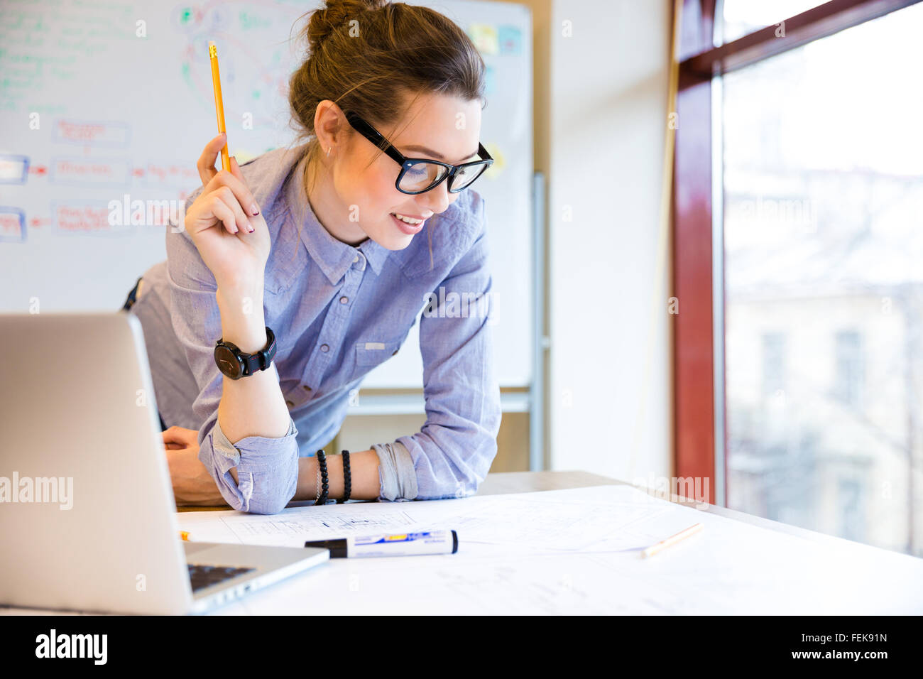 Happy young woman in glasses standing near the window in office and working with blueprint - Stock Image