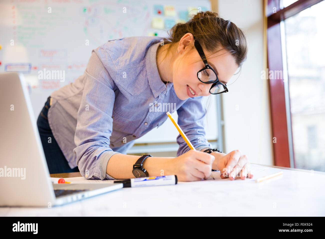 Smiling pretty young woman drawing blueprint on the table near the window - Stock Image