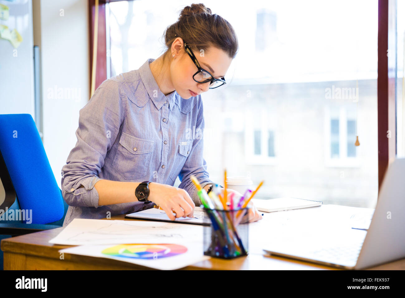 Concentrated pretty young woman fashion designer sitting and drawing sketches in office - Stock Image