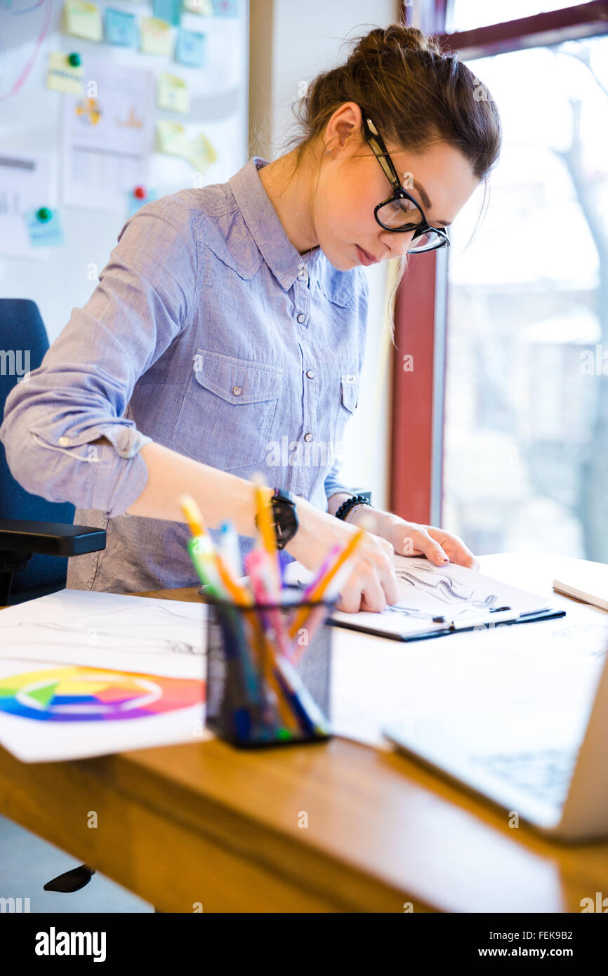 Focused beautiful young woman fashion designer in glasses drawing sketches on workplace - Stock Image
