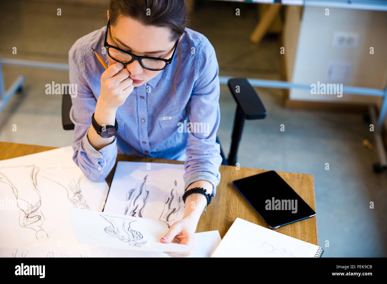 Top view of pensive pretty young woman fashion designer sitting on workplace and looking at sketches - Stock Image