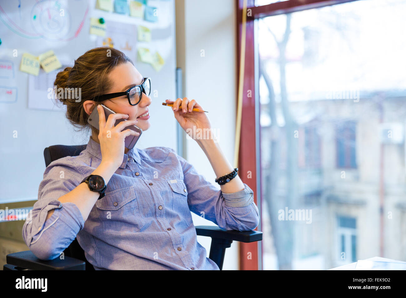 Happy beautiful young business woman in glasses sitting and talking on cell phone in office - Stock Image